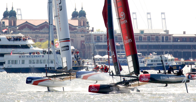 Emirates TNZ tries to hold off a flying Groupama Team France.  Ellis Island is in the background.